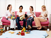 Four Women Sit on a Sofa With Babies on Their Laps