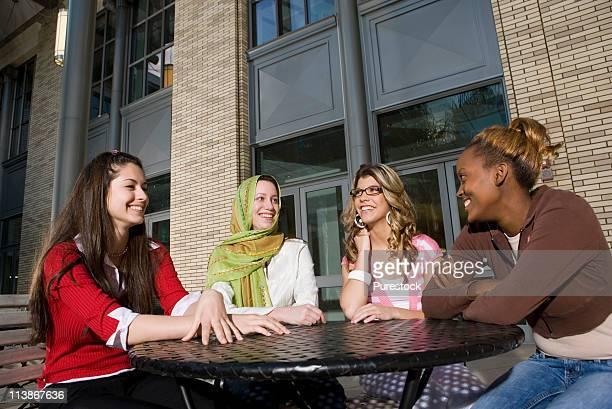 Four women sitting at a table outside a building, socializing and conversing