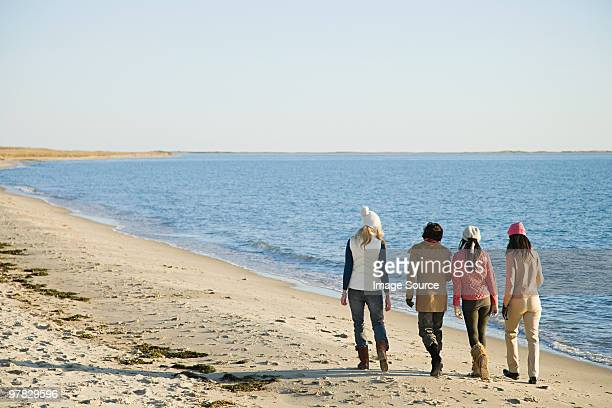 Four women walking by sea