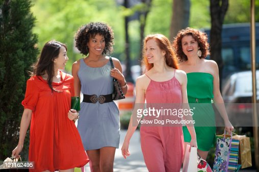 Four Women Walking City Street with Shopping Bags : ストックフォト