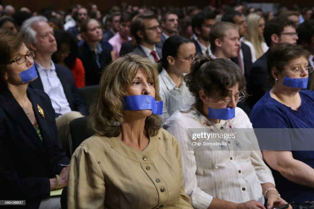 Four women wear blue tape over their mouths as a silent protest during a hearing of the Senate Judiciary Committee about political donations and freedom of speech in the Hart Senate Office Building June 3, 2014 in Washington, DC. Liberal political groups delivered two million petitions calling for a campaign finance constitutional amendment and pushing for '...a proposed constitutional amendment to restore the ability of Congress and the states to regulate the raising and spending of money in elections.'