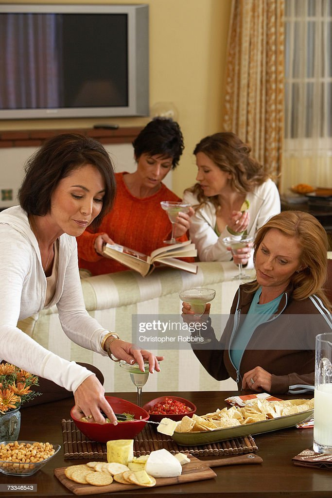 Four women with cocktails and appetizers in room