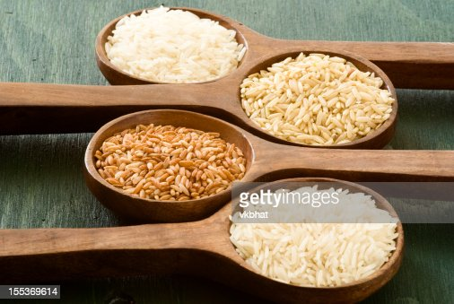 Four wooden spoons holding different types of rice