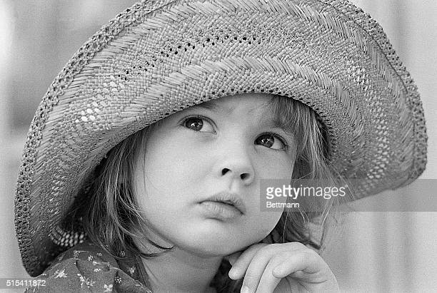 Four year old Drew Barrymore the youngest member of the Barrymore and Drew families looks upward wearing a straw hat