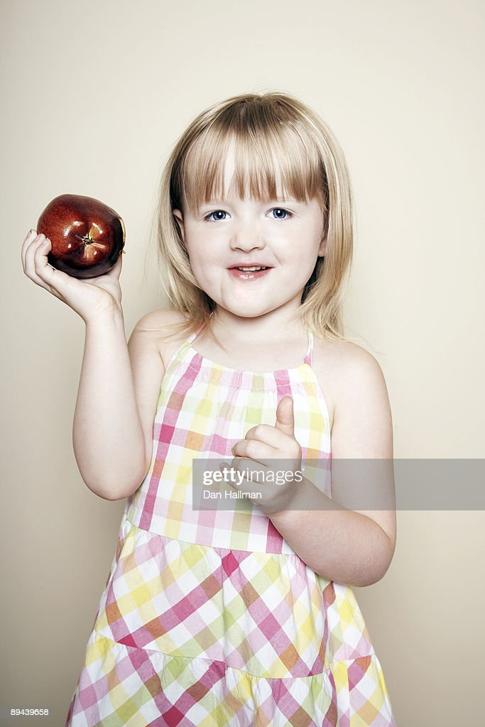 Four year old girl holding an apple. : Stock Photo