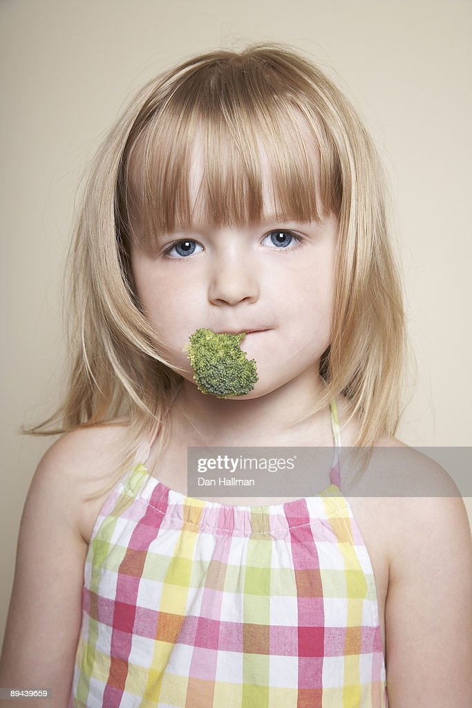 Four year old girl holding broccoli in mouth. : Stock Photo