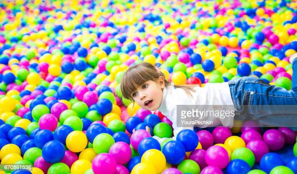 Four year old girl in a pool of coloured balls