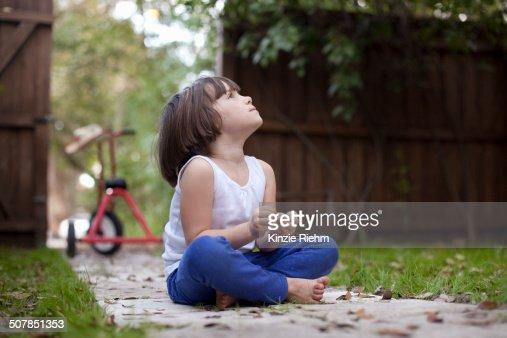 Four year old girl sitting on garden path gazing upward
