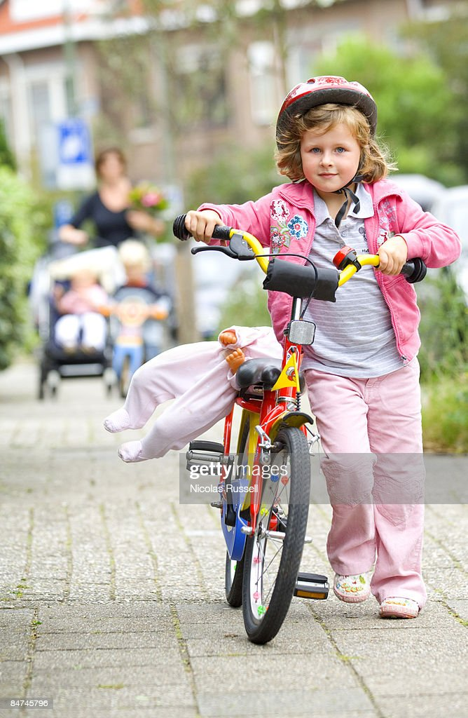 four year old girl walking home with bike : Stock Photo