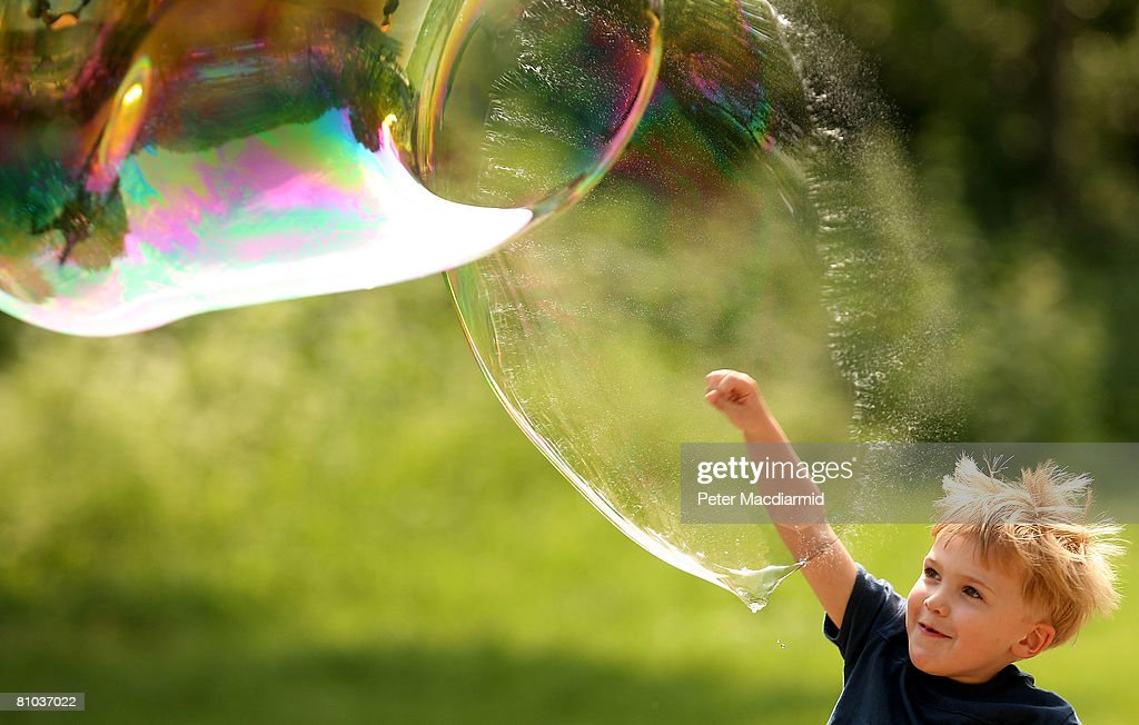 Four year old Kaleb Stanley from Dublin punctures a giant bubble on London's South Bank on May 9, 2008 in England. The south east of England has enjoyed higher than normal temperatures.