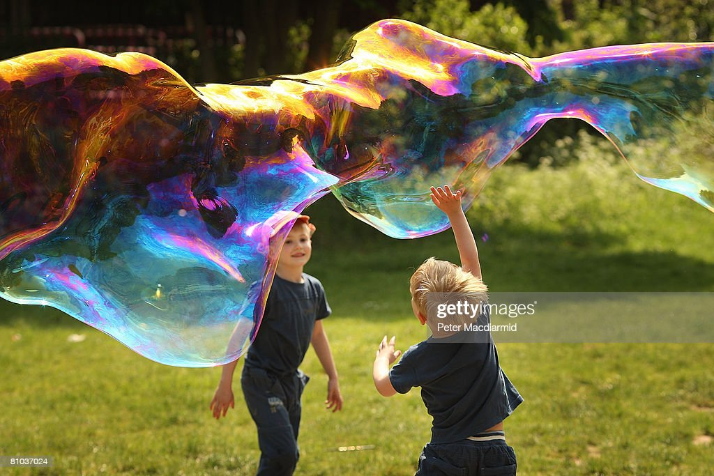 Four year old Kaleb Stanley (R), from Dublin, reaches up to puncture a giant bubble with the help of his seven year old brother Jacob on London's South Bank on May 9, 2008 in England. The south east of England has enjoyed higher than normal temperatures.