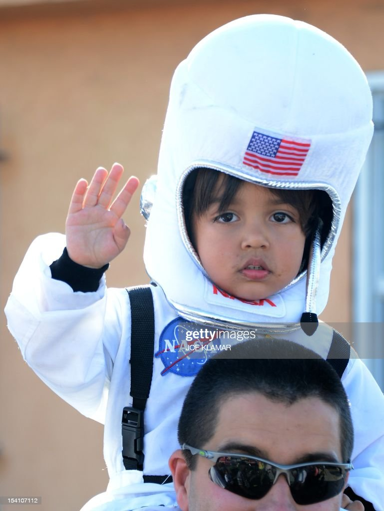 Four year old Levi is watching The Space Shuttle Endeavour is transported through the streets of Los Angeles on its final journey to its permanent museum home on October 13, 2012 in Inglewood, California. The 170,000-pound (77,272 kg) shuttle will travel at no more than 2 mph (3.2 km per hour) along a 12-mile (19km) route from Los Angeles International Airport (LAX) to its final home at the California Science Center. NASA's space shuttle program ended in 2011 after 30 years and 135 missions. AFP PHOTO/JOE KLAMAR