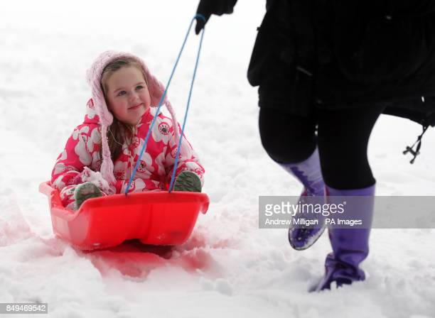 Four year old Madisyn Mcfadyen plays on a sledge with mum Lisa and dog Bailly after heavy snowfall overnight in Auchterarder