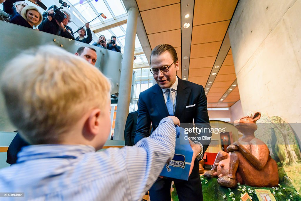 Four year old Pontus (L) hands over a baby romper suit in a present box reading the name of German capitols football club 'Hertha BSC' in a attends the opening of the exhibition 'Frech, wild & wunderbar - schwedische Kinderbuchwelten' at the Swedish Embassy on April 11, 2016 in Berlin, Germany.