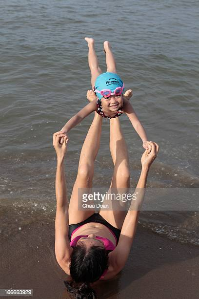 A four yearold Vienamese girl plays with her mother on Cua Lo beach which is about 300 kms south of Hanoi Though the water is as not as clear like...