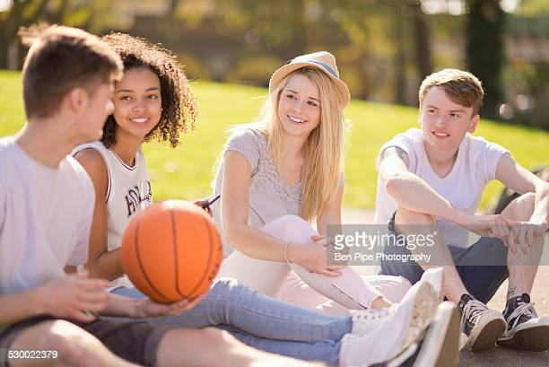Four young adult basketball players sitting chatting