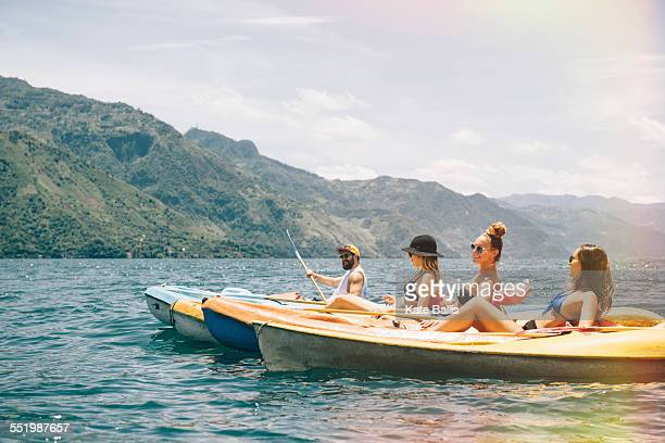 Four young adult friends kayaking on Lake Atitlan, Guatemala