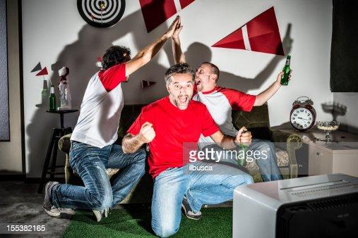 Four young adult men friends watching football: High-five goal!