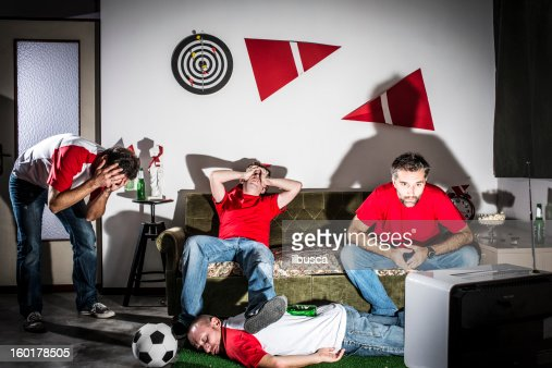 Four young adult men friends watching football on television: Defeat