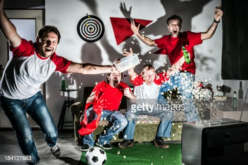 Four young adult men friends watching football on television: Goal!