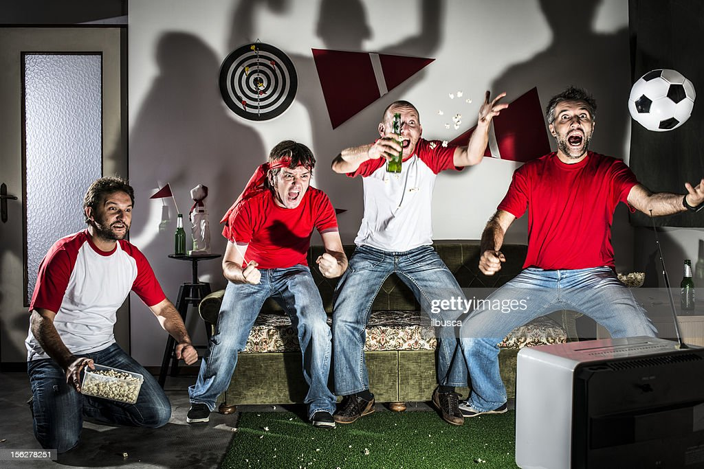 Four young adult men friends watching football on television: Goal! : Stock Photo