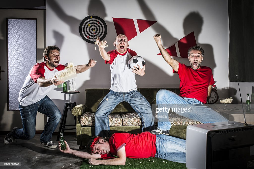 Four young adult men friends watching football on television: Goal : Stock Photo