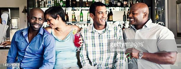 Vier junge Erwachsene genießen Sie einen Drink in der hotel bar