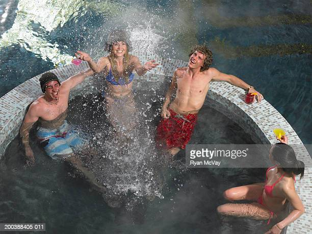Four young adults in hot tub, one woman splashing, elevated view