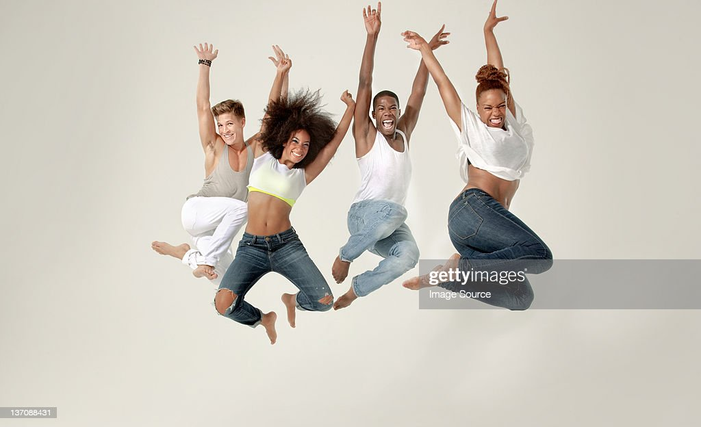 Four young adults jumping in the air with joy : Stock Photo