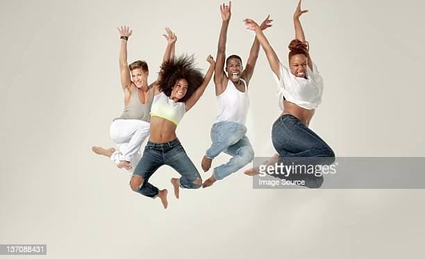 Four young adults jumping in the air with joy