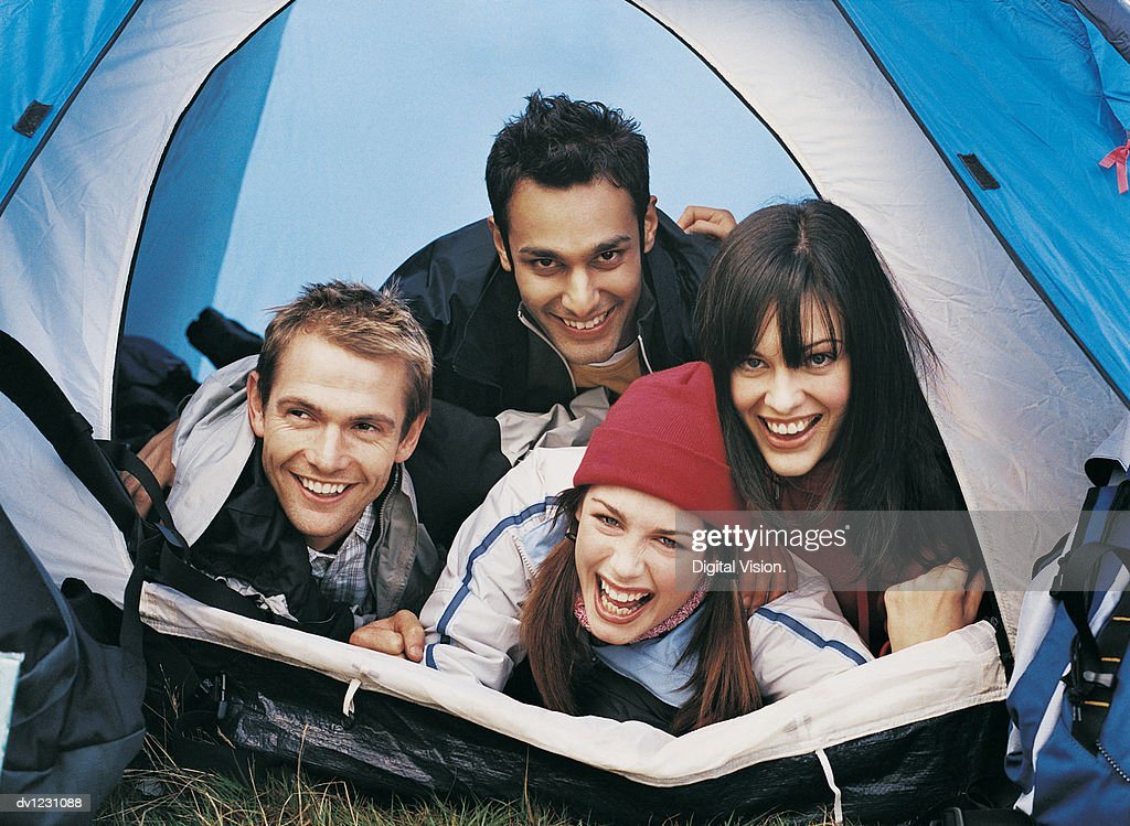Four Young Adults Lying On Top of Each Other in a Tent : Stock Photo