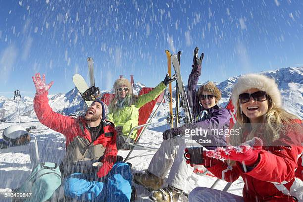 Four young adults relaxing on ski slope