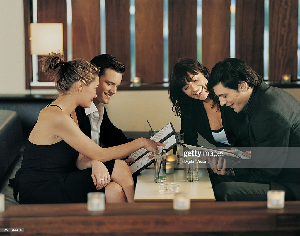 Four Young Adults Sitting at a Table and Reading a Menu : Stock Photo