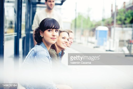 Four young adults sitting at tram station