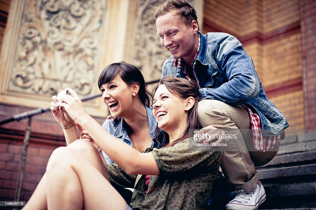 Four young adults using smart phone : Stock Photo