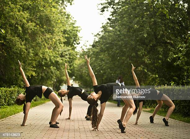 Four young ballet dancers exercising in park