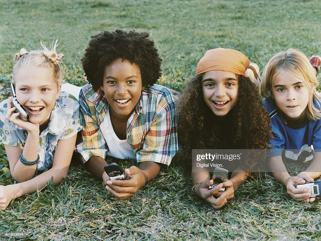 Four Young Boys and Girls Lie on the Grass in a Line, Holding Mobile Phones : Stock Photo