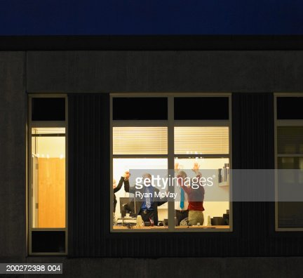 Four young businesspeople celebrating in office, view through window : Stock Photo