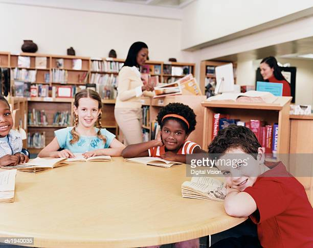 Four Young Children Sitting Around a Table in a Library