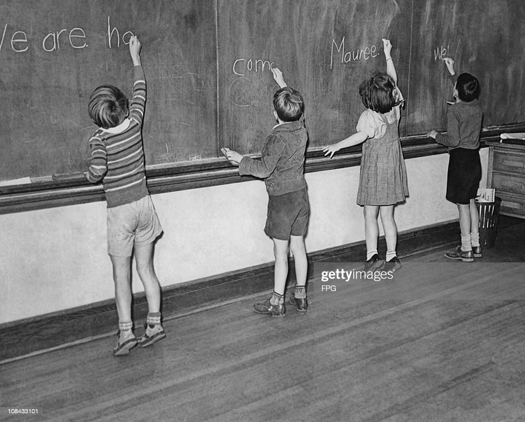 Four young children writing on the classroom blackboard circa 1950.
