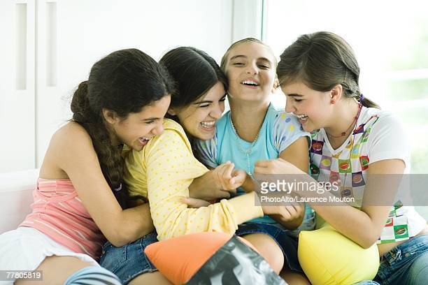 Four young female friends tickling each other and giggling