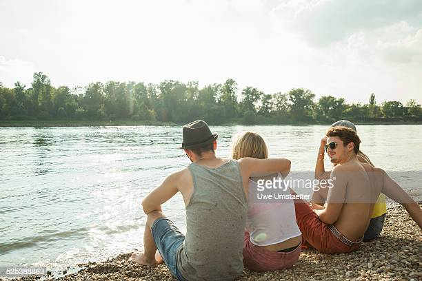 Four young friends sitting on lakeshore