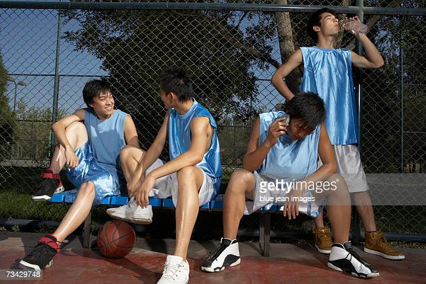 Four young men in blue jerseys sit on a bench on an outdoor basketball court, two talking, one making a call on his cell phone and one drinking water.