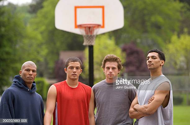 Four young men on basketball court, portrait