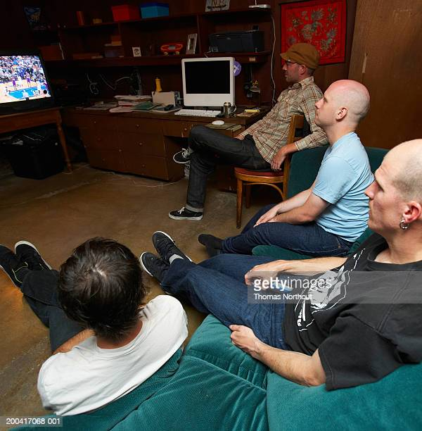 Four young men watching television