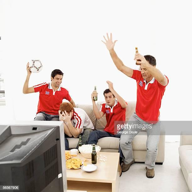 four young men wearing soccer jerseys