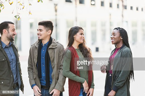 Four young multi-ethnic adults talking outside building : Stockfoto