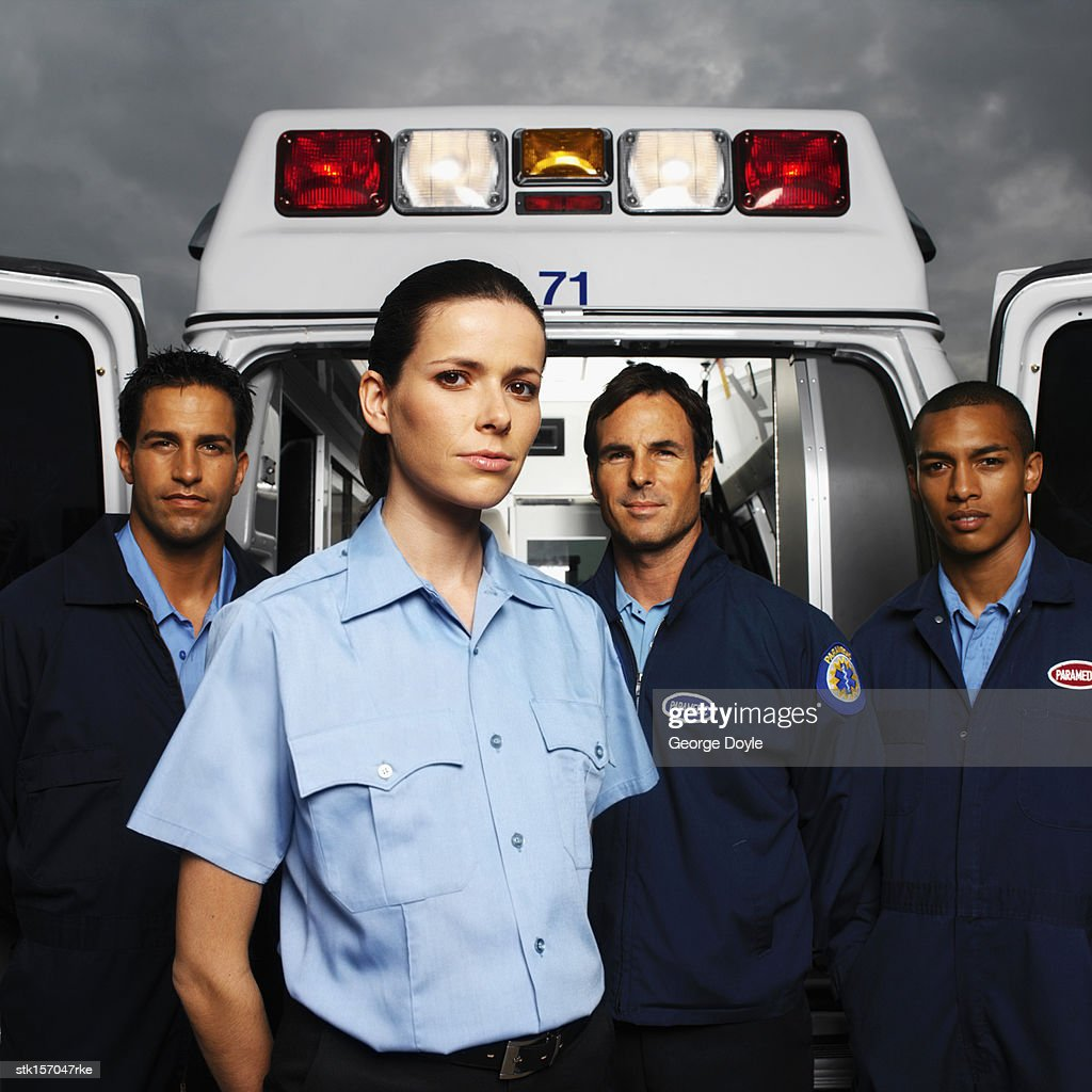 Four young paramedics standing at the rear of an ambulance