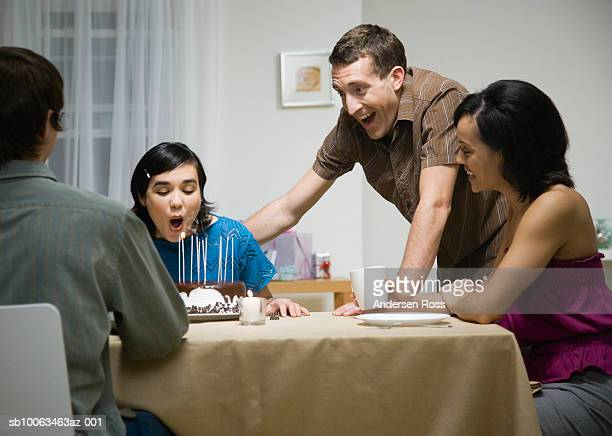 Four young people at dinner party, one woman blowing out candles on birthday cake, at home