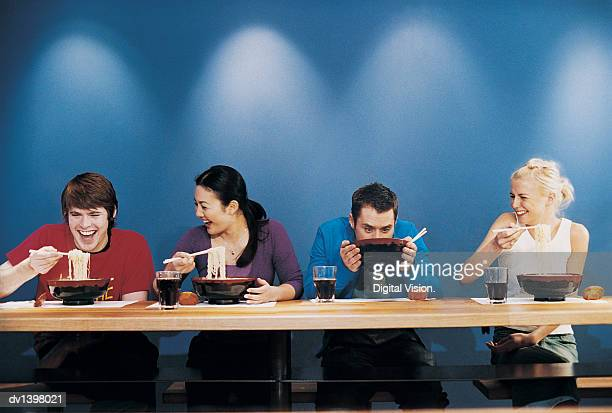 Four Young People Eating Noodles From Bowls at a Table in a Japanese Restaurant